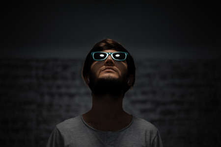Dark portrait of young guy looking up, wearing sunglasses, using wireless earphones.