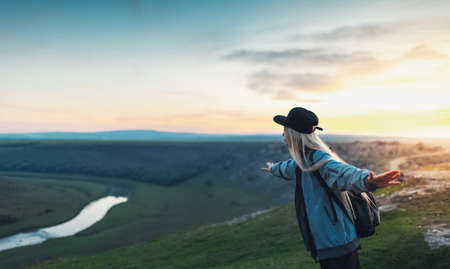 Young happy blonde girl with black backpack and cap, holding hands like airplane on peak of hills at sunset. Travel concept.