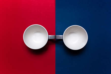 Top view of two ceramic mugs on background of red and blue colors.