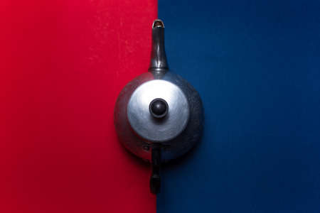 Top view of vintage aluminum teapot on two backgrounds of red and blue colors.
