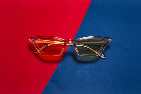 Close-up of modern fashion yellow glasses on background of red and blue colors.