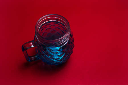 Close-up of blue glass mug for juice on dark background of red color.