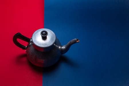 Top view of vintage aluminum teapot, on two dark backgrounds of red and blue colors with copy space. Stok Fotoğraf