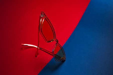Close-up of modern fashion yellow transparent glasses on two backgrounds of red and blue colors.