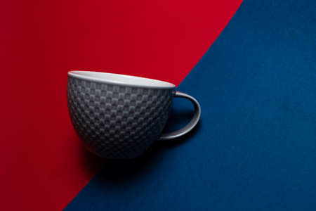 Close-up of grey mug on two backgrounds of red and blue of colors.