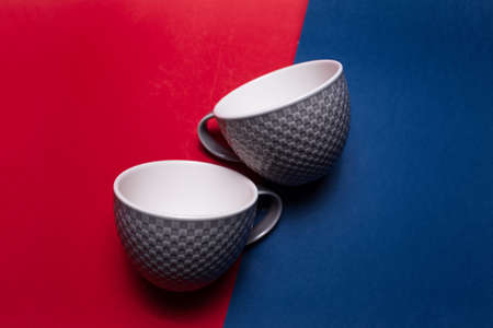 Close-up of two ceramic grey mugs on two backgrounds of red and blue colors.