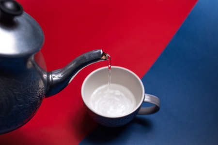 Close-up of aluminum teapot pouring water in ceramic mug, on two backgrounds of red and blue colors. Top view.