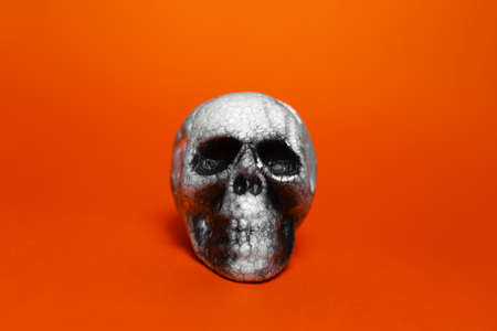Close-up of anatomical human spooky skull on background of orange or lush lava color.