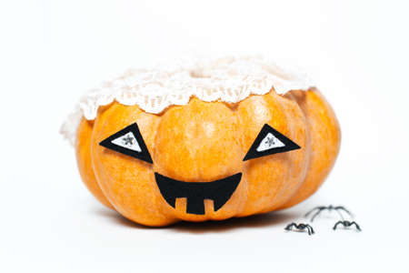Studio portrait of halloween smiling pumpkin of orange color, wearing lace veil near spiders. Isolated on white background.