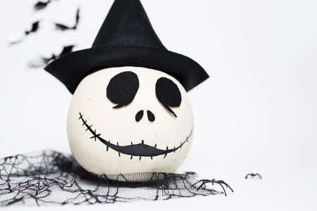 Studio portrait of white halloween smiling pumpkin with black hat. Isolated on white background.