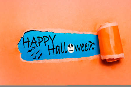 Happy Halloween text on blue background in hole of orange torn paper.