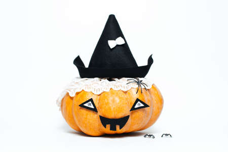 Studio portrait of happy halloween pumpkin of orange color, wearing black hat, isolated on white background.