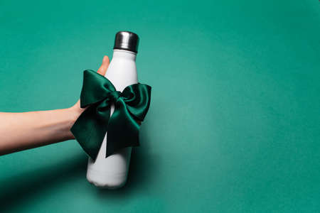 Close-up of female hand holding reusable steel thermo water bottle of white color with green bow like gift, on green background with copy space. Stok Fotoğraf