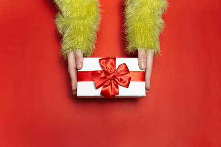 Top view of female hands in green sweater, holding a white gift box with red ribbon on background of red color. Stok Fotoğraf
