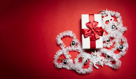 Top view of white gift box with red bow, decorated with Christmas toys, on background of red color with copy space. Stok Fotoğraf