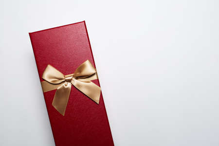 Close-up of Christmas gift box of red color with golden bow, isolated on white background with copy space.
