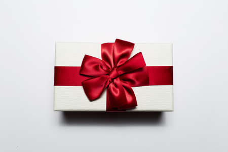Close-up of Christmas gift box of white color with red bow, isolated on white background.