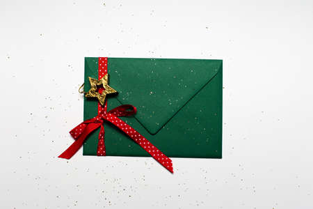 Close-up of Christmas envelope of green color decorated with star toy, red ribbon and glitter, isolated on white background.