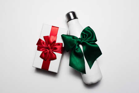 Close-up of gift box and reusable steel thermo water bottle with red and green bows. Isolated on white background. Stok Fotoğraf