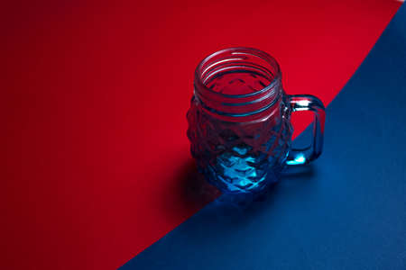 Close-up of glass mug for juice on dark background of red and blue color. Stok Fotoğraf