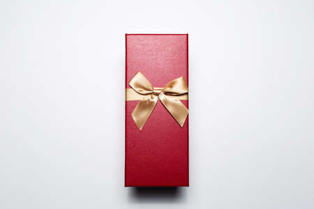 Close-up of gift box of red color with golden bow, isolated on white background.