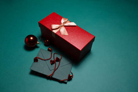 Christmas concept. Close-up of red gift box and paper envelope with decorations on green background.