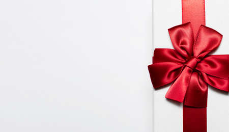 Close-up of white gift box with red bow isolated  on white background with copy space for text.