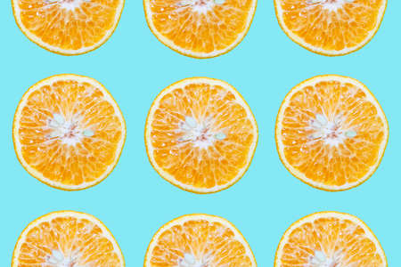 Colorful pattern of cutted orange fruits, isolated on background of cyan or aqua menthe color.