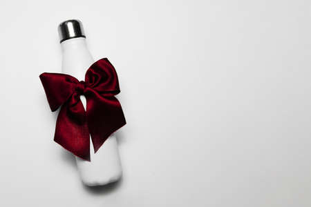 Close-up of reusable steel thermo water bottle with red bow like gift, isolated on white background with copy space.