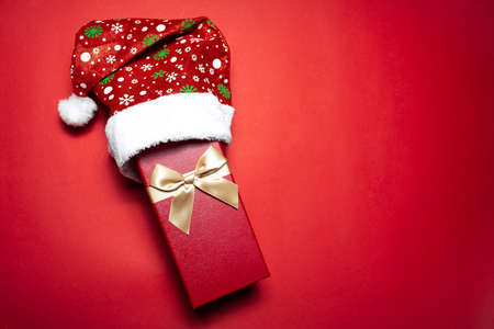 Top view of red gift box with golden bow wearing Santa hat on background of textured wall of red color with copy space.