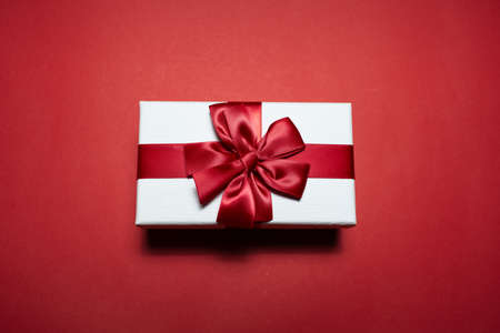 Close-up of white gift box with red bow, on red background. Stok Fotoğraf