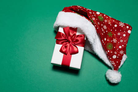 Top view of white gift box with red bow wearing Santa hat on background of green color with copy space.
