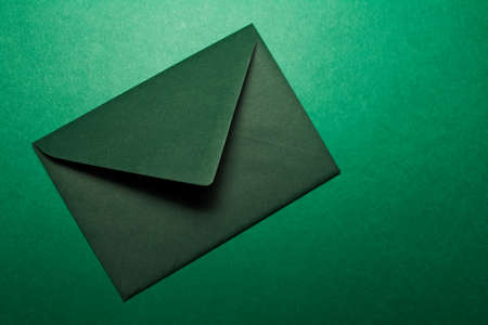 Close-up of paper envelope of green color isolated on background of textured green wall.