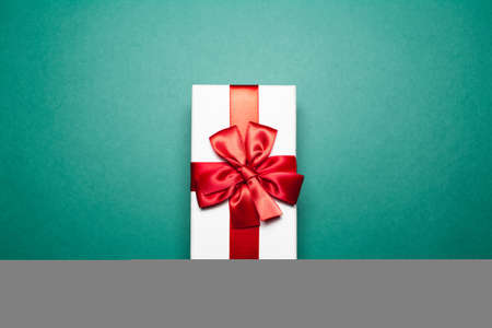 Close-up of white gift box with red bow, on green background.