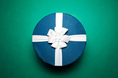 Close-up of blue gift box with white bow, on green background.