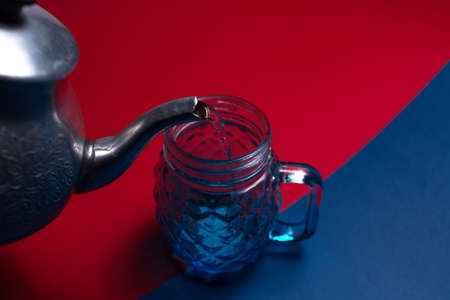 Close-up of aluminum teapot pouring water in glass mug for juice, on two backgrounds of red and blue colors. Top view.