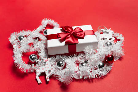 Close-up of white gift box with red bow, decorated with Christmas toys, on background of red color.