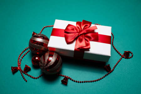 Close-up of white gift box with red bow near Christmas tree toys on green background. Stok Fotoğraf