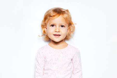 Studio portrait of cheerful child girl with curly blonde hair on background of white color.