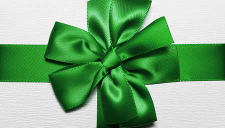 Close-up of green wrapping ribbon in shape of bow for white gift box.