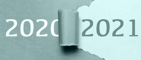 Happy new year, new start, new page of life; resolution concept. Text of 2021 on background in hole of torn paper with text of 2020. Tidewater green of color. Stockfoto