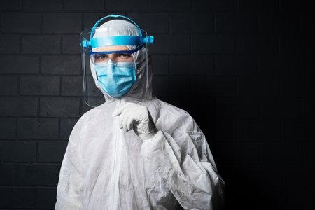 Studio dark portrait of young doctor man wearing PPE suit