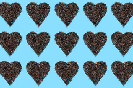 Pattern of pumpkin seeds in shape of hearts on blue background. 免版税图像