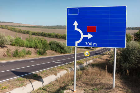 Blue road sign showing direction near highway. Stok Fotoğraf