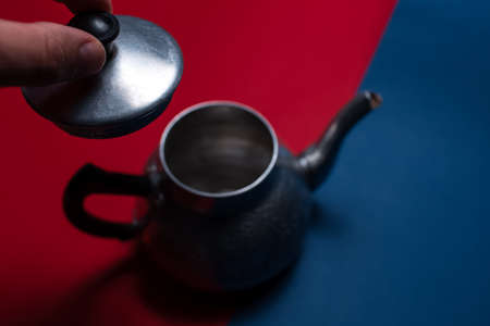 Close-up of male hand take off the cap of aluminium vintage teapot. Red and blue backgrounds. Stok Fotoğraf