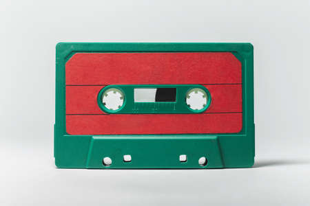 Close-up of green-red vintage music cassette on white background. Studio object image.