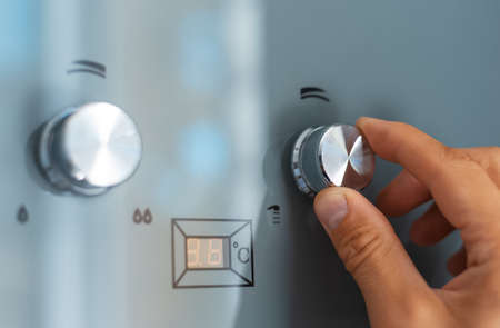 Close-up of male hand adjusting temperature of water heater. Modern home gas fired boiler. Stok Fotoğraf