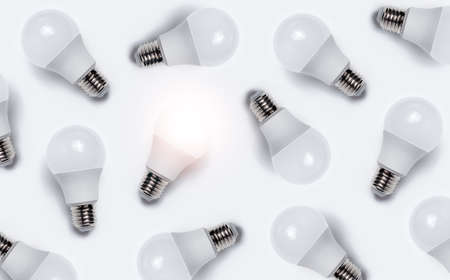 Pattern of luminous bulb between other with no lights bulbs. Creative idea concept.