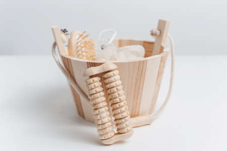 Close-up of wooden massager tool near small bucket with other bath accessories against white studio background.