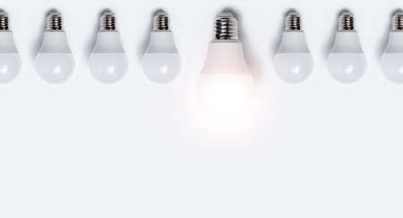 Close-up of many light bulbs with one glowing against white background. Business idea concept with copy space. Stok Fotoğraf